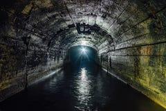 Zmrok zalewający beton sklepiał drenażu kopalniany tunel zdjęcia stock