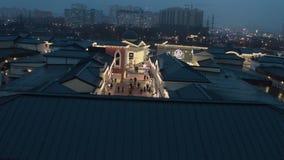 Zmroku dachu wierzchołki, sklepów budynki z iluminacją i budowy tło, zdjęcie wideo