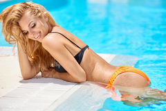 Zmysłowa blond dziewczyna w pływackim basenie Fotografia Stock