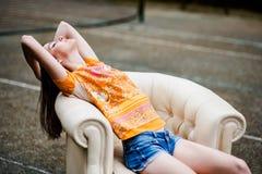 Zmysłowa elegancka młoda kobieta relaksuje na białej skóry leżance Zdjęcia Royalty Free