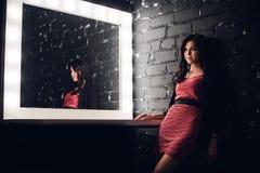 Zmysłowa kobieta w ciemnym pokoju Nowożytny elegancki, i uzupełnialiśmy stół z żarówkami fotografia stock