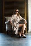 zmysłowa kobieta w okularach przeciwsłonecznych i klasycznym okopu żakieta pozować obraz royalty free