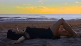 Zmysłowa młoda brunetki kobieta kłama i relaksuje na piaskowatej plaży przy zmierzchem zbiory wideo