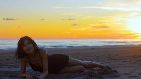 Zmysłowa młoda brunetki kobieta ma zabawy lying on the beach na piaskowatej plaży przy zmierzchem zdjęcie wideo