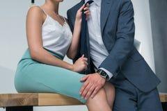 Zmysłowy bizneswomanu obsiadanie na stołu i mienia krawacie męski kolega Fotografia Stock