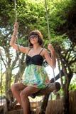 Zmysłowy czuły dziewczyny obsiadanie na huśtawce jest ubranym piękną suknię Długiego ciemnego włosy Huśtawka jest na plaży z zdjęcia royalty free