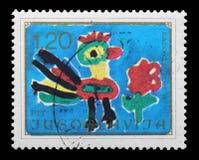 Znaczek drukujący w Jugosławia pokazuje koguta i kwiatu, Children rysunek, radość Europa Fotografia Stock