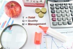 Znaczenie TQM z dokumentem, pieniądze, zegar, jabłko, kalkulator Zdjęcia Royalty Free