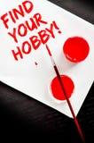 Znajduje twój hobby tekst malującego na białym papierze Zdjęcie Stock