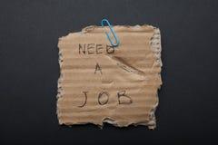 Znak «ty potrzebujesz pracę «na poszarpanym kartonie, czarny tło zdjęcia royalty free
