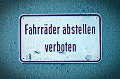 Znak i prohibicja podpisujemy z ostrzeżeniem w niemiec Zatrzymuje bicykle zabraniających w angielskich parking rowerach no pozwol Zdjęcia Stock