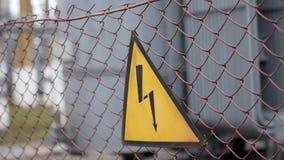 Znak ostrzegawczy na niebezpieczeństwie elektryczność Znak na ogrodzeniu elektrownia zbiory