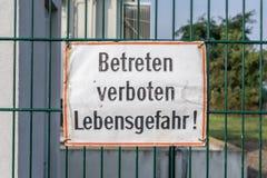Znak ostrzegawczy na ogrodzeniu z niemieckimi słowami niebezpieczeństwo życie! - no wchodzić do - fotografia royalty free