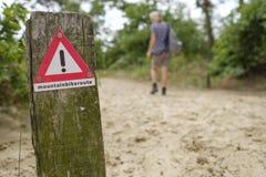 Znak ostrzegawczy w lesie dla halnych rowerzystów Obrazy Stock