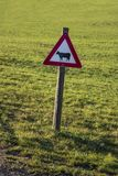 Znak ostrzegawczy z projektującą czarną krową obrazy royalty free