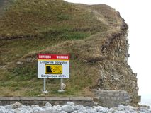 Znak przedstawia niebezpieczne falezy na otoczak plaży w UK obraz stock