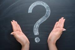 Znak zapytania, rysująca kreda na blackboard z girl& x27; s ręka zdjęcie stock