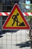 Znaka ostrzegawczego ` w budowie ` dołącza metal siatki ogrodzenie z czerwonym i biel paskującym sygnału klepnięciem obraz royalty free