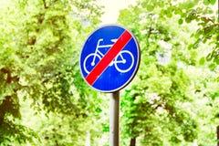 Znaki dla cyklistów, drogowy znak przeciw tłu zieleni drzewa Fotografia Stock