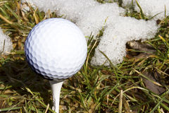 Znaki wiosna, piłka golfowa na trójniku z śniegiem Zdjęcia Stock