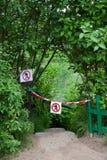 Znaki z znaka przejściem zakazującym, spadków schodki zestrzelają wśród krzaków Obrazy Royalty Free