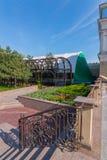 Znakomity krajobraz w parku z łóżkami, drzewami i niebieskim niebem kwiatu, Piękni kędzierzawi poręcze blisko kroków tylko Obraz Stock