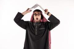 Zniechęcony Arabski mężczyzna w keffiyeh trzyma laptop zdjęcia stock