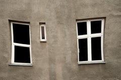 Zniekształcający okno z biel ramą na popielatej starej ściennej architekturze obraz stock