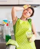 Znużony gospodyni domowej obmycia wnętrze w kuchni zdjęcie stock