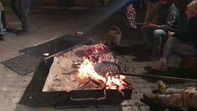 25/08/18 Zocca, Modena - kastanjefestival Groep vrienden die kastanjes op het vuur koken stock video