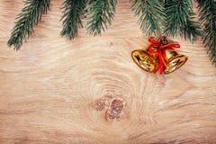 Złociści Bożenarodzeniowi dzwony i jedlinowa gałąź na nieociosanym drewnianym tle Fotografia Royalty Free