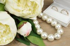 Złociste obrączki ślubne, Perełkowa kolia i peonia kwiaty, Zakończenie Zdjęcia Royalty Free
