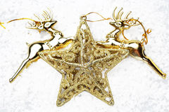 Złocisty gwiazdy i złota renifer na śniegu dla dekoracj bożych narodzeń Zdjęcia Royalty Free