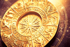 Zodiac. A gold zodiac wheel over a horoscope Stock Photography