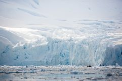 Zodiac - tiny beside immense ice cliffs - explores Paradise Bay, Antarctica royalty free stock image