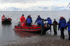 Zodiac boats ferry passengers to shore during a Christmas cruise. NEKO HARBOR, ANTARCTICA - DEC 11 - Zodiac boats ferry passengers to shore during a Christmas Royalty Free Stock Photo