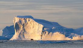 A zodiac full of tourist viewed against a large iceberg with the light of the midnight sun, Antarctica royalty free stock images
