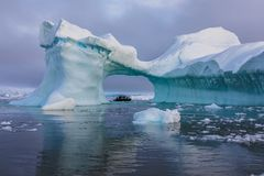 A zodiac full of tourist viewed through an arch in a large iceberg, Antarctica. A zodiac full of tourist viewed through an arch in a large blue iceberg with Royalty Free Stock Image