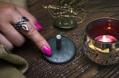 Zodiac wheel talisman. Horoscope amulet. Astrology. Zodiac talisman in female hand in the lights of burning candle. Horoscope wheel. Astrology royalty free stock photos