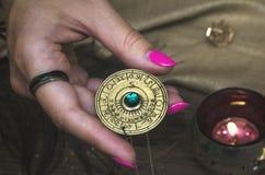Zodiac wheel talisman. Horoscope amulet. Astrology. Zodiac talisman in female hand in the lights of burning candle. Horoscope wheel. Astrology stock images