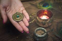 Zodiac wheel talisman. Horoscope amulet. Astrology. Zodiac talisman in female hand in the lights of burning candle. Horoscope wheel. Astrology royalty free stock photography