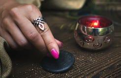 Zodiac wheel talisman. Horoscope amulet. Astrology. Zodiac talisman in female hand in the lights of burning candle. Horoscope wheel. Astrology stock photos