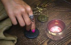 Zodiac wheel talisman. Horoscope amulet. Astrology. Zodiac talisman in female hand in the lights of burning candle. Horoscope wheel. Astrology royalty free stock image