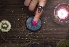 Zodiac wheel talisman. Horoscope amulet. Astrology. Zodiac talisman in female hand in the lights of burning candle. Horoscope wheel. Astrology royalty free stock photo