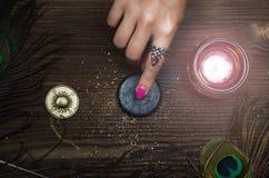 Zodiac wheel talisman. Horoscope amulet. Astrology. Zodiac talisman in female hand in the lights of burning candle. Horoscope wheel. Astrology stock photography