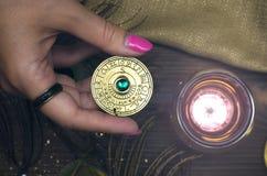 Zodiac wheel talisman. Horoscope amulet. Astrology. Zodiac talisman in female hand in the lights of burning candle. Horoscope wheel. Astrology stock photo