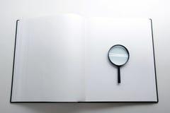 Zoek met vergrootglas, die informatie in boeken, blauwdrukken, tijdschriften zoeken Controleinspectie Exemplaar ruimtetekst Stock Foto's