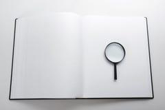 Zoek met vergrootglas, die informatie in boeken, blauwdrukken, tijdschriften zoeken Controleinspectie Exemplaar ruimtetekst Royalty-vrije Stock Foto