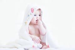 Zoet babymeisje in een dwars-gestikte met de hand gemaakte handdoek Stock Foto's