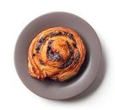 Zoet broodje met chocoladeschilfers op grijze die plaat op wit, hierboven wordt geïsoleerd van royalty-vrije stock fotografie